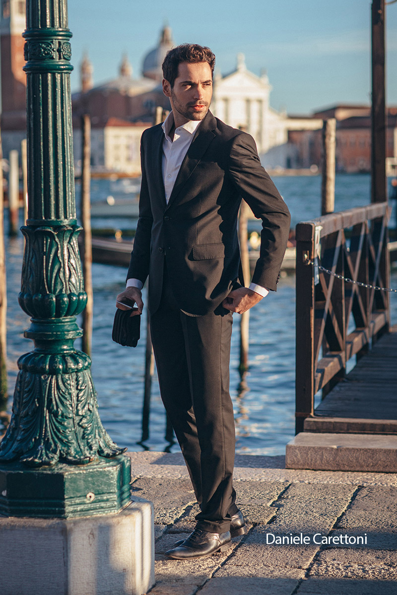 LARAS Brand testimonial Deniele Carettoni respectable businessman in a suit on the shore of Venice, the dream of every woman gold dress